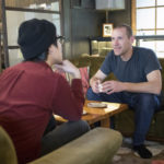 Two men meeting and chatting in a coffee shop